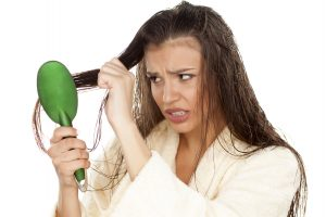 young nervous woman in bathrobe brush her moist hair